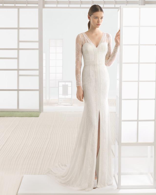 Vestido de novia silueta de encaje y pedrería con escote y espalda en pico y apertura delantera, en color natural.