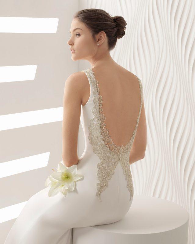 Dulce y sensual. Este vestido realizado con organza juega con un cuerpo corazón de guipur con pedrería. Sin duda, la cintura ceñida junto a un original broche floral, aportan gran dulzura.