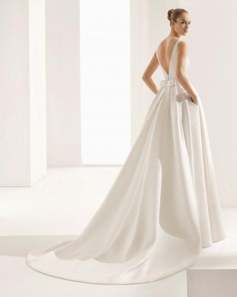 Vestido de novia estilo clásico en brocado cenefa, con escote barco, espalda V, cola extraible y bolsillos.