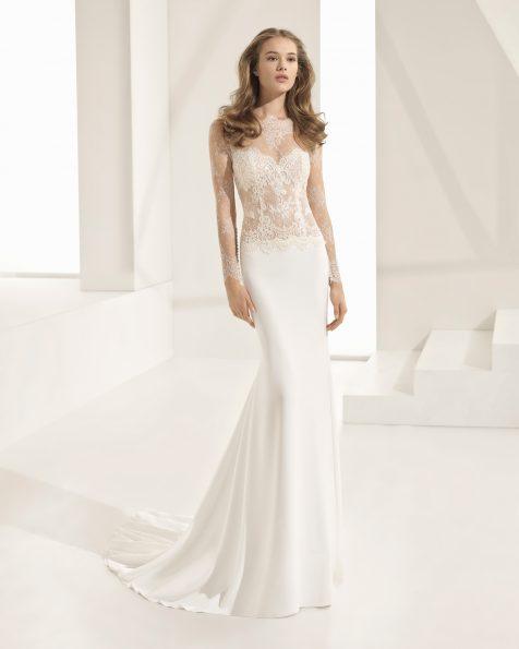 Vestido de novia corte recto de encaje pedrería y crepe, con manga larga,escote barco y transparencias.