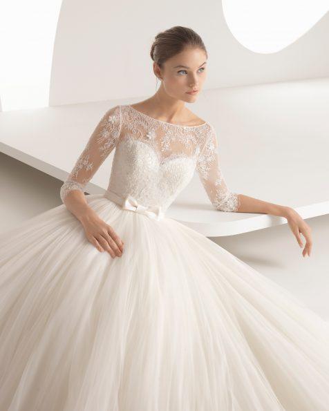 Rochie de mireasă în stil prințesă din dantelă, strasuri și tul subțire, cu mânecă lungă și decolteu iluzie cu spatele acoperit.