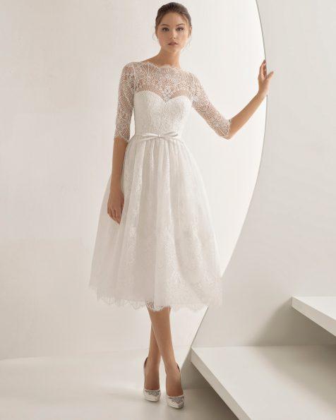 Rochie de mireasă în stil prințesă scurtă din dantelă și strasuri, cu mânecă lungă și decolteu iluzie cu spatele acoperit.