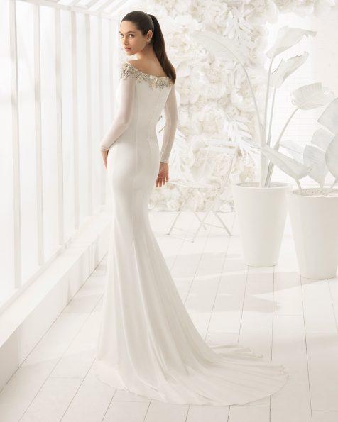 Robe de mariée coupe sirène en crêpe à manches longues et col bateau avec fleurs en cristal brodées.