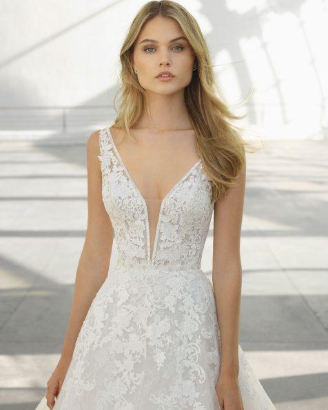 Romantisches Brautkleid aus Spitze mit Strassbesatz. Deep-Plunge-Ausschnitt und tief ausgeschnittener Rücken. Erhältlich in Naturweiß. Kollektion ROSA CLARA 2019.