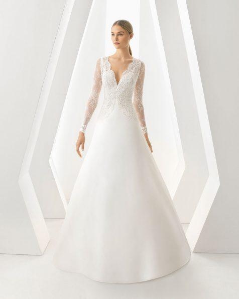 Vestido de novia corte evasé de organza, encaje y pedrería. Escote V y manga larga. Disponible en color natural. Colección ROSA CLARA 2019.