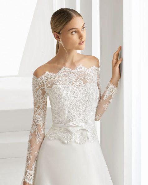 Vestido de noiva corte evasé de renda, brilhantes e organza. Decote envolvente e laço na cintura. Disponível em cor natural. Coleção ROSA CLARA 2019.