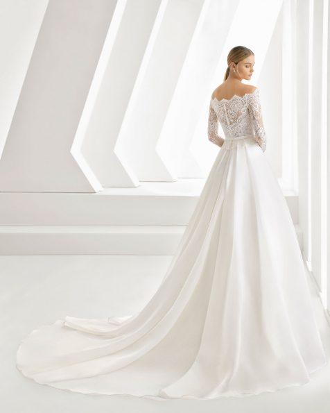 Robe de mariée coupe évasée en dentelle, pierreries et organza. Col enveloppant et nœud à la taille. Disponible en couleur naturelle. Collection ROSA CLARA 2019.