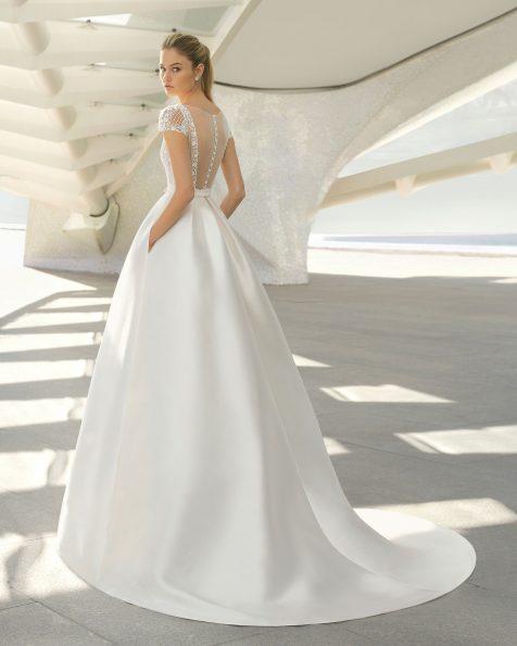 Vestido de novia estilo clásico en tamís y pedrería. Manga corta y espalda escotada. Disponible en color natural. Colección ROSA CLARA 2019.