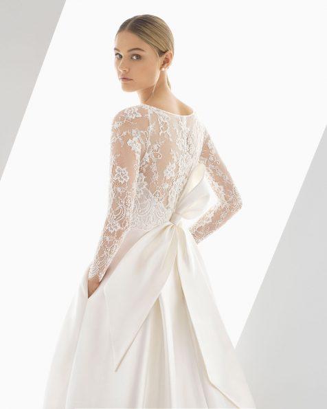Robe de mariée coupe classique en tamis, dentelle et pierreries. Corsage à manches longues et nœud dans le dos. Disponible en couleur naturelle. Collection ROSA CLARA 2019.