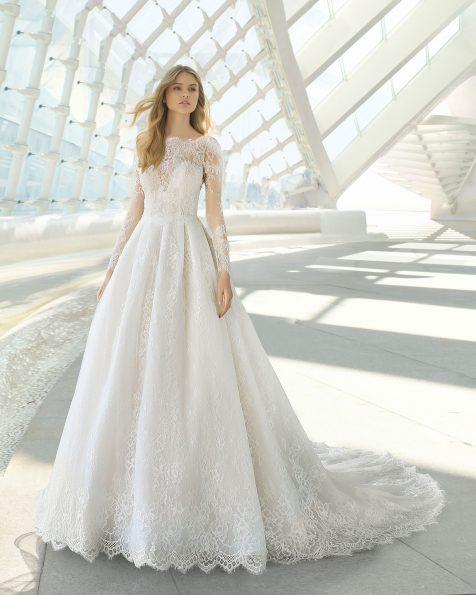 Vestido de novia estilo princesa de encaje y pedrería. Escote bateau y manga larga. Disponible en color natural. Colección ROSA CLARA 2019.