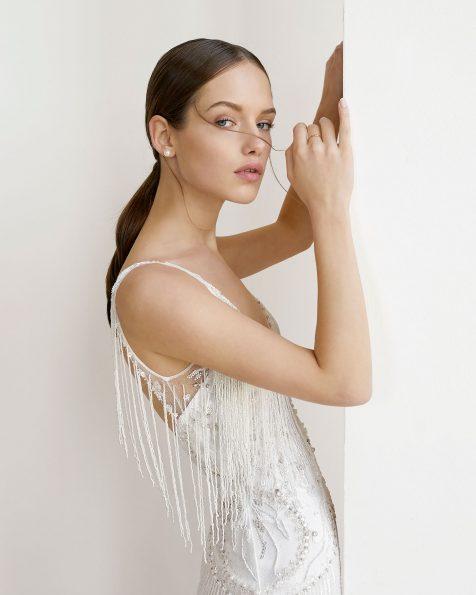 Vestido de novia corte recto de pedrería y flecos. Escote ilusión sobre escote corazón y espalda escotada. Disponible en color natural. Colección ROSA CLARA SOFT 2019.
