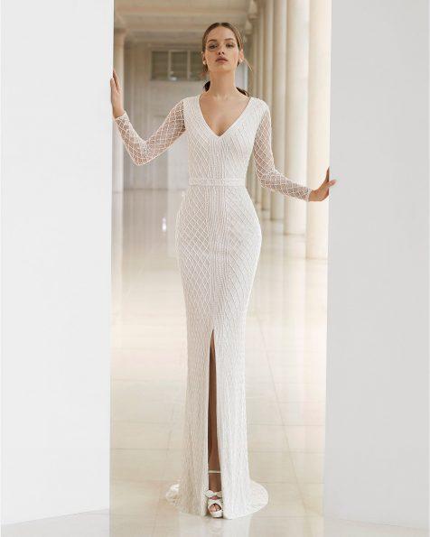 Vestido de novia corte recto de pedrería. Escote V y        abertura delantera. Con manga larga. Disponible en c        olor natural. Colección ROSA CLARA SOFT 2019.