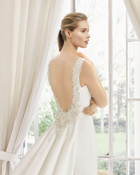 Vestido de novia corte recto y cola de cloqué, con espalda joya de pedrería frost muy pronunciada, en color natural.