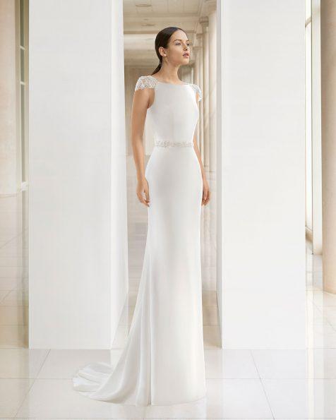 Vestido de novia corte recto de crepe con escote barco y espalda joya en pedrería frost, en color natural.