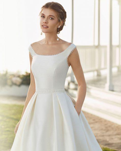 Vestido de noiva estilo clássico de sienna e renda de brilhantes na cintura. Com decote à barco sem mangas e costas em V. Coleção ROSA CLARA 2020.