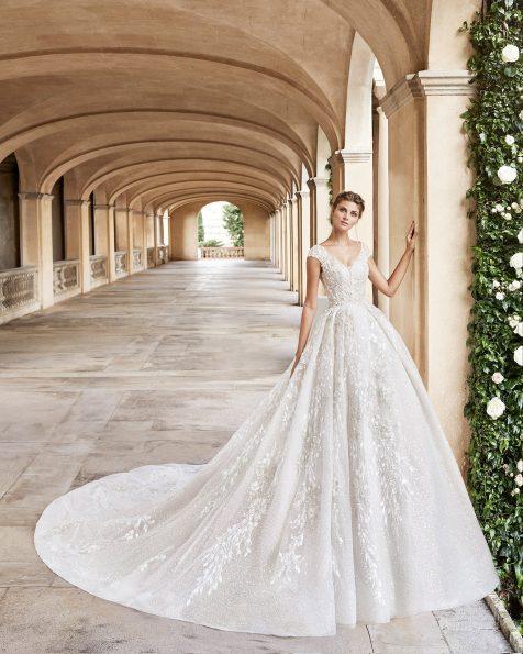 Vestido de novia estilo princesa de encaje y pedrería. Escote redondo, manga corta de encaje y espalda escotada con corsé. Falda gran volumen. Colección MARTHA BLANC 2020.