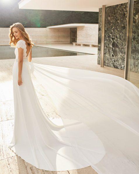 Vestit de núvia lleuger de crepè i blonda rebrodé. Escot suau barca, esquena escotada i màniga curta. Amb faixí d'adornament de blonda lineal amb pedreria i cua extraïble. Col·lecció ROSA CLARA COUTURE 2021.