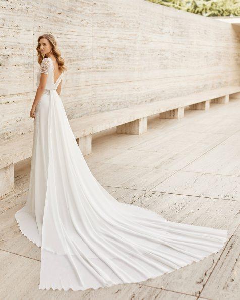 Robe de mariée légère en crêpe georgette et guipure dans le dos et sur les manches. Corsage blousant, col bateau, décolleté dans le dos et manches courtes. Avec ornement de points ajourés type