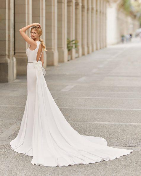 Vestit de núvia i sobrecua tall recte de crepè elàstic i pedreria a la cintura. Amb escot en V i obertura rodona a l'esquena. Amb llaç d'organdí en sobrecua. Col·lecció ROSA CLARA 2021.
