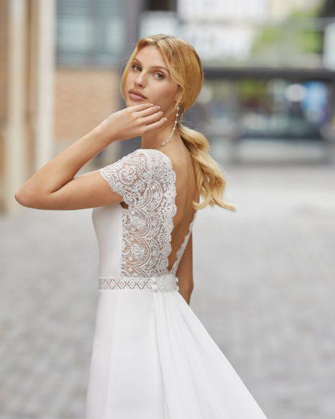 Schmales Brautkleid mit abnehmbarer Schleppe aus elastischem Crêpe mit Strassbesatz an der Taille und den kurzen Ärmeln. U-Boot-Ausschnitt und V-Rückenausschnitt mit Spitzen- und Strassbesatz. Kollektion ROSA CLARA 2021.