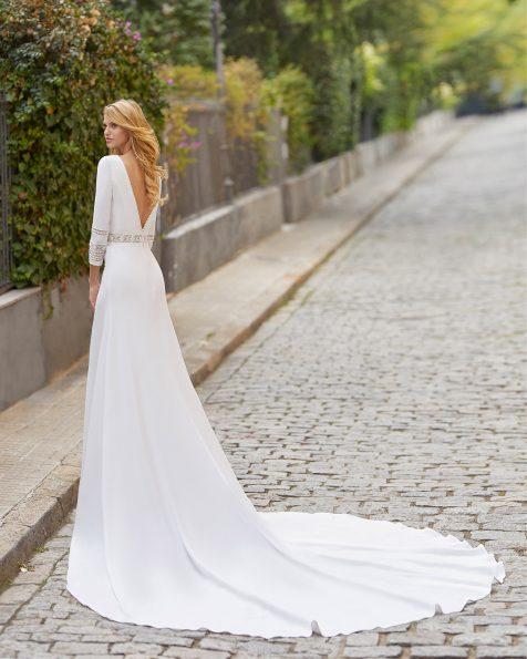 Vestido de novia corte recto de crepe elástico con escote barco y espalda en V. Con puntilla de encaje y pedrería en cintura y en mangas 3/4. Colección ROSA CLARA 2021.