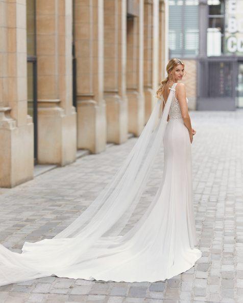 Robe de mariée et tombants en tulle coupe droite en crêpe élastique et dentelle avec pierreries sur le col et la ceinture. Col en V et décolleté dans le dos, sans manches. Collection ROSA CLARA 2021.