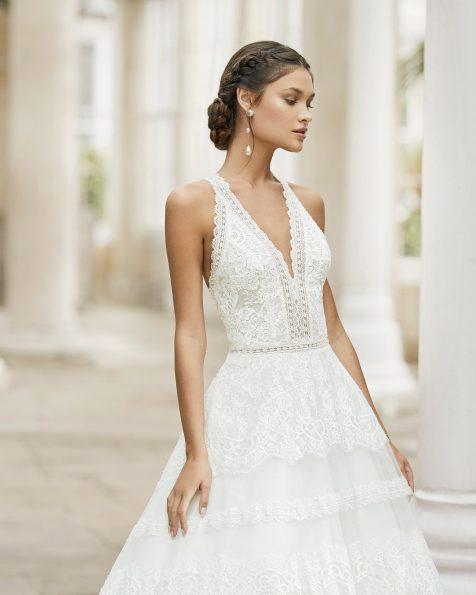 Vestido de noiva de estilo em A de tule com renda e brilhantes no decote e no cós. Decote deep-plunge e costas com alças cruzadas de renda e brilhantes. Coleção ROSA CLARA 2021.