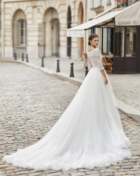 Vestido de noiva estilo princesa de tule suave na saia e corpo de renda de brilhantes com manga a 3/4. Decote à barco com decote interior em forma de coração e costas fechadas. Coleção ROSA CLARA 2021.