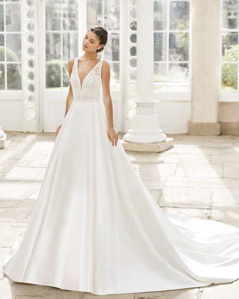 Vestido de noiva estilo clássico de cetim imperial e renda de brilhantes. Decote deep-plunge e costas decotadas com laço. Coleção ROSA CLARA 2021.