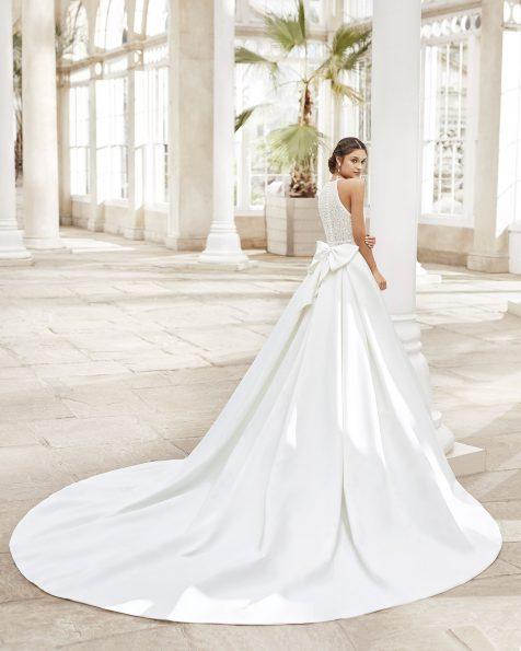Vestit de núvia estil clàssic en ras imperial amb blonda i pedreria en escot i cinturilla amb escot hàlter i llaç a l'esquena. Col·lecció ROSA CLARA 2021.