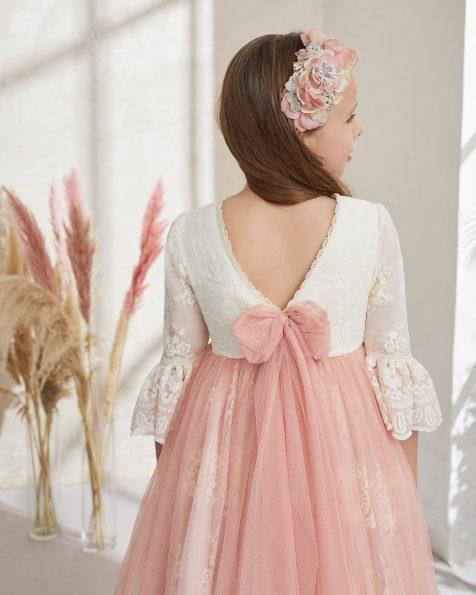 Romantisches Kommunionkleid mit Empire-Taille aus besticktem Tüll. Carré-Ausschnitt, spitzer Rückenausschnitt und französische Ärmel mit Volant aus Spitze und Tüll. Mit Überrock aus Tüll, Blumenverzierung an der Taille und Schleife am Rücken. Kollektion ROSA CLARA FIRST 2021.