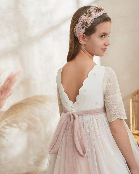 Romantisches Kommunionkleid mit Empire-Taille aus besticktem Tüll. Runder Ausschnitt und spitzer Rückenausschnitt mit welliger Einfassung, kurze Ärmel. Mit geschlitztem Rock, gebundenem Taillenband aus Tüll und Blumenverzierung an der Taille. Kollektion ROSA CLARA FIRST 2021.