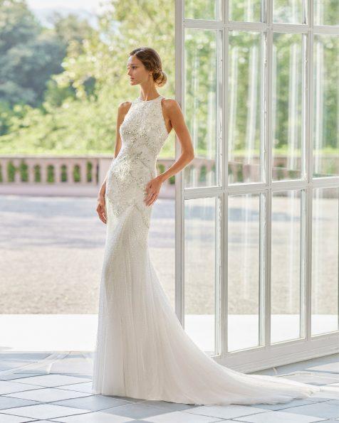 Vestido de novia de corte sirena de pedrería y tul suave con escote halter y espalda bordada con pedrería. Disponible en color natural/plata y natural. Colección  2022.