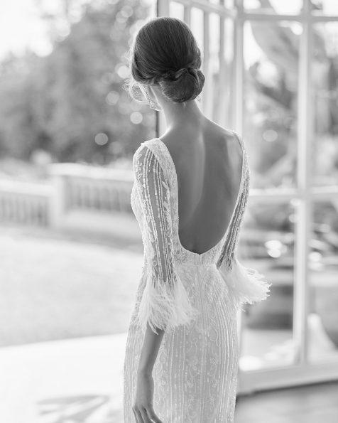 Abito da sposa in strass dal taglio dritto, con scollo deep-plunge e schiena scollata, maniche francesi e piume. Disponibile in bianco naturale/avorio. Collezione  2022.