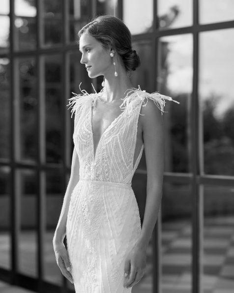 Vestido de novia corte recto de pedrería con escolte deep-plunge y espalda en V con plumas en hombros y capa tul plumeti en interior de la falda. Disponible en color natural/nácar. Colección  2022.