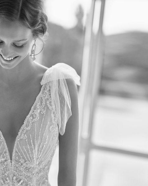 Vestido de novia corte recto de pedrería con escote deep-plunge y espalda en V con caídas/lazos de tul plumeti en hombros. Disponible en color natural/champagne. Colección  2022.