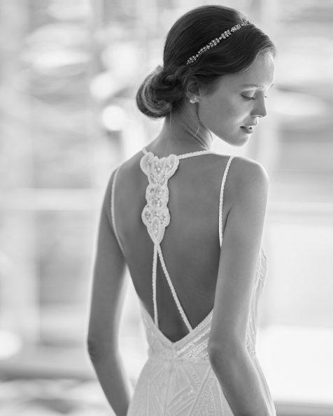Vestido de novia corte recto de pedrería con escote deep-plunge y detalle joya en la espalda y capa tul plumeti en interior de la falda. Disponible en color natural. Colección  2022.