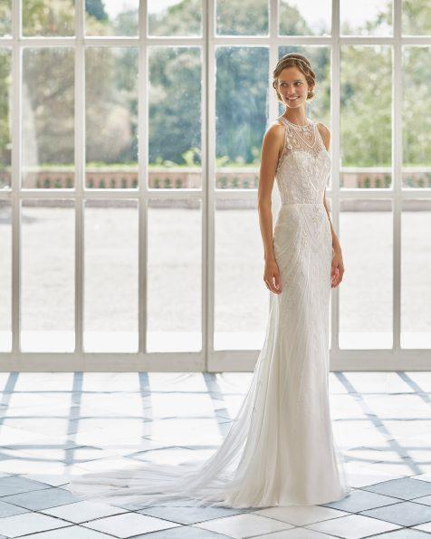 Vestido de novia corte recto de pedrería, escote halter con espalda de pedrería y capa tul plumeti en interior de la falda. Disponible en color natural/champagne. Colección  2022.