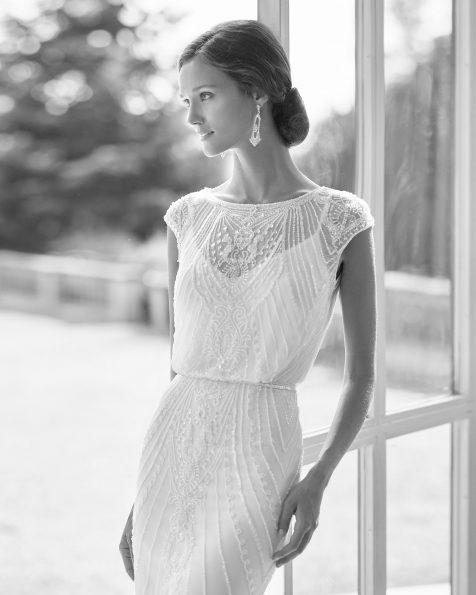 Vestido de novia y viso de corte recto de pedrería y gasa de seda, con escote barco y manga corta. Vestido ablusado. Disponible en color natural. Colección  2022.