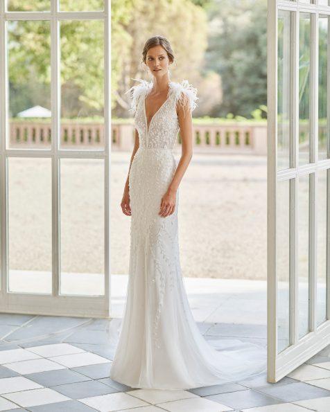 Vestido de novia corte recto de pedrería con escolte deep-plunge y espalda escotada. Con plumas en los hombros y capa tul plumeti en interior de la falda. Disponible en color natural. Colección  2022.