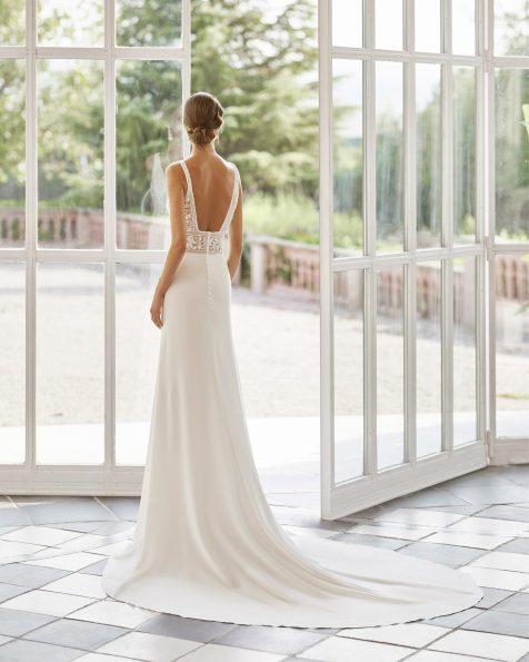Vestido de novia estilo linea A de crep elástico y pedrería, con escote deep-plunge y espalda escotada. Disponible en color natural. Colección  2022.