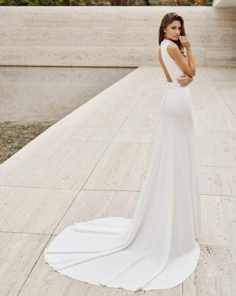 Abito da sposa elegante dal taglio dritto; scollo all'americana e apertura sulla schiena. Modello esclusivo di Rosa Clará, confezionato in crêpe elasticizzato con fodera modellante. Collezione ROSA CLARA 2022.