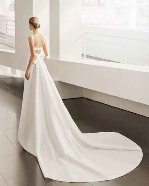 Vestido y cola de novia de estilo clásico de corte A; con escote barco y espalda escotada y lazo. Modelo de Rosa Clará de novia hecho en sienna. Colección ROSA CLARA 2022.