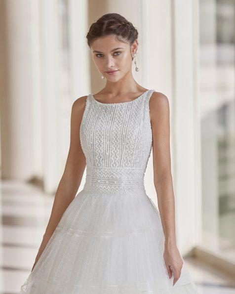 Vestido de novia de estilo romántico; con escote barco y espalda tirantes. Modelo de Rosa Clará de novia hecho en tul flocado, encaje y pedrería. Colección ROSA CLARA 2022.