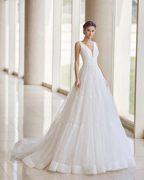 Robe de mariée de style romantique ; avec décolleté et dos en V. Modèle de Rosa Clará pour mariée réalisé en tulle floqué, crêpe et dentelle à la taille. Collection ROSA CLARA 2022.
