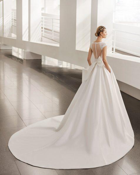 Klassisches Brautkleid; mit Deep-Plunge-Ausschnitt, transparenter Rückenpartie aus Plumetis-Tüll und mit Ranglanärmeln und Schleife am Rücken. Brautkleid Rosa Clará aus Sienna und Spitze. Kollektion ROSA CLARA 2022.
