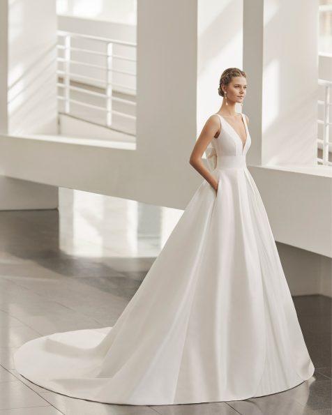Vestido de novia de estilo clásico; con escote deep plunge y espalda escotada, con lazo espalda y bolsillos. Modelo de Rosa Clará de novia hecho en sienna. Colección ROSA CLARA 2022.